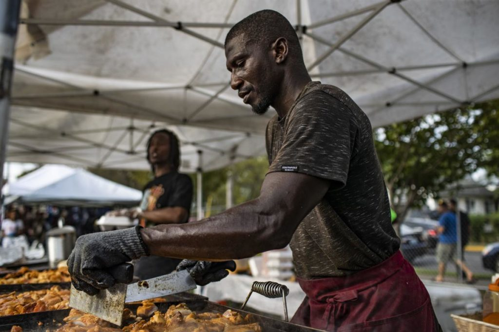 Amidoe Conate of Atlanta prepares jerk chicken during the International Festival on Saturday, September 28, 2019, at Circus Square Park. (Austin Anthony, bgdailynews.com)